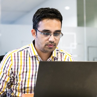 Person working on mobile device with open laptop in background