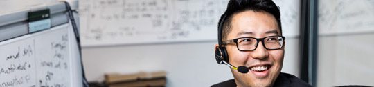 A smiling tech industry employee wearing a headset