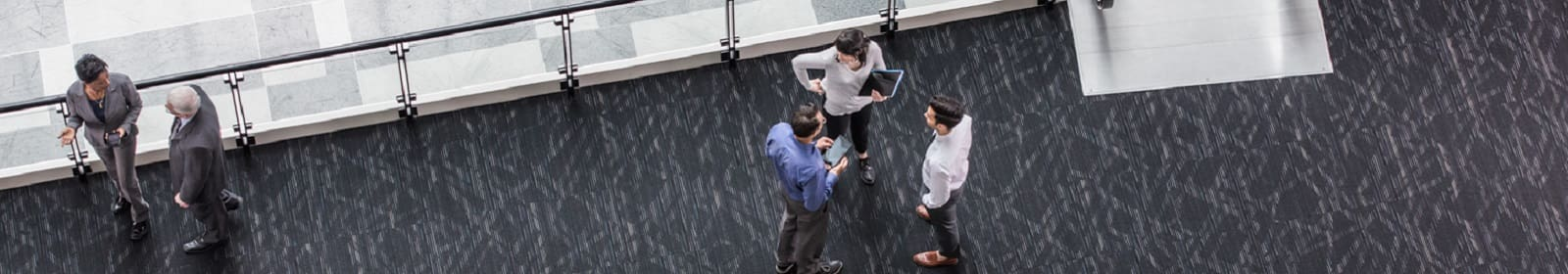 Employees chat on an elevated walkway in an office building