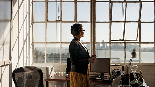 Woman standing in office looking out window