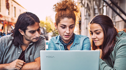 Three students gathered around laptop outside