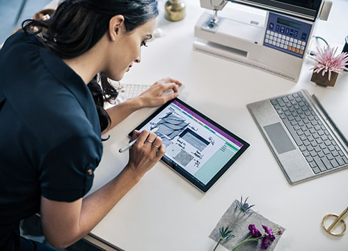 Woman working on tablet at desk