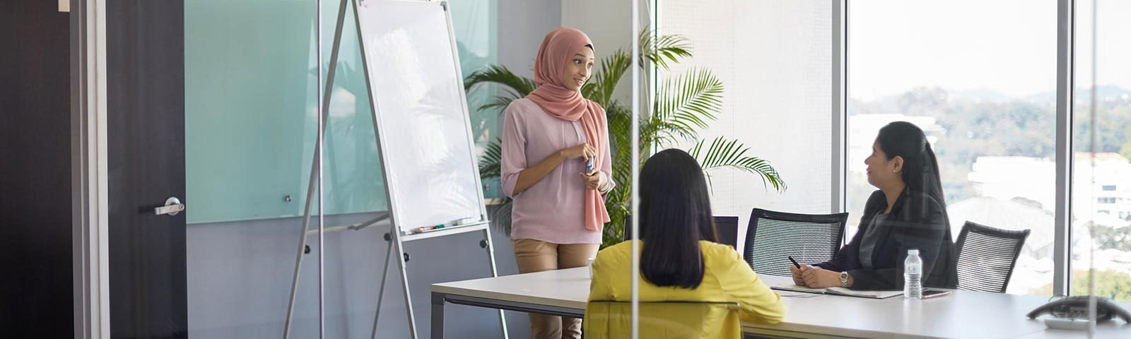 three women discussing in meeting room