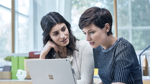 Two coworkers looking at a Surface laptop