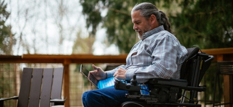 Person in wheelchair sitting outside, working on laptop.