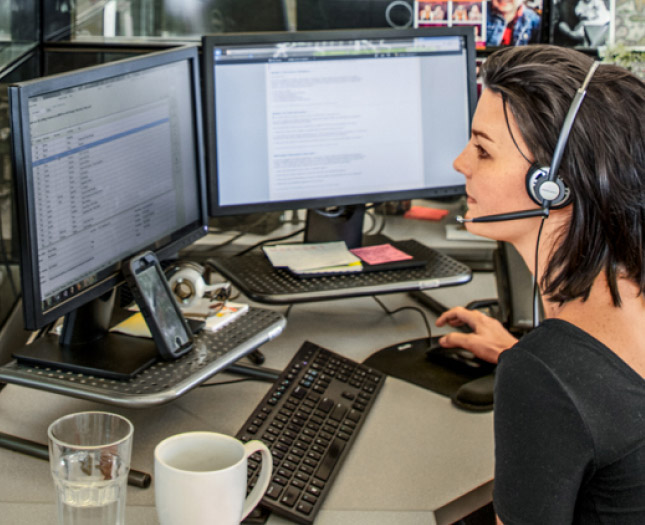 Business woman in front a computer with two monitors engaging on a call.