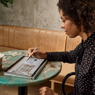 Woman sitting at a table using a stylus to write on a tablet