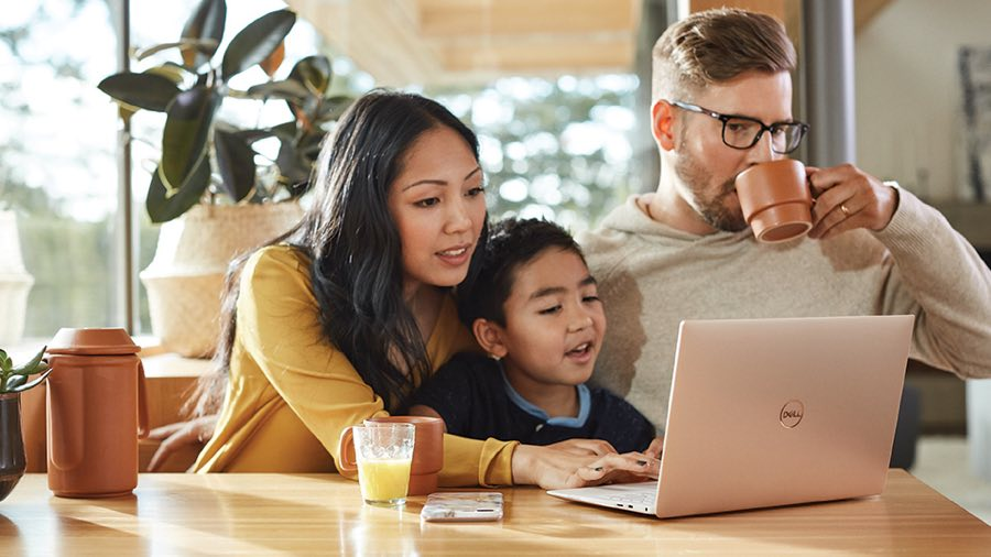 Family sitting at a table looking at a laptop together