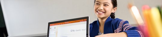 Child smiling and sitting in front of a laptop