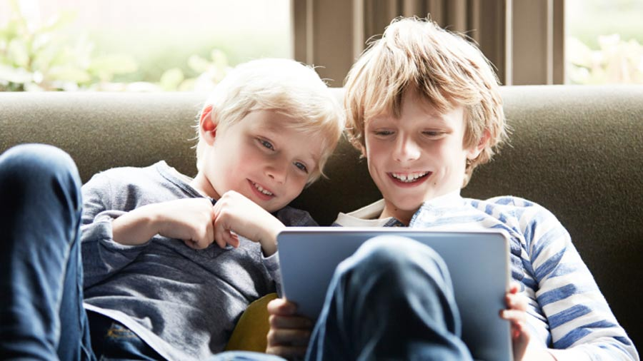 Two kids on couch smiling looking at a tablet