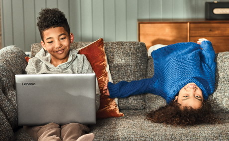 Two kids on a couch laying down and using a laptop