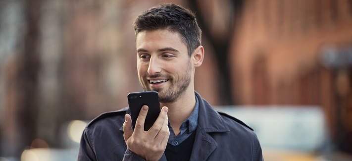 A man laughs as he speaks into his phone during what appears to be a video chat. He has a small beard and a big smile.