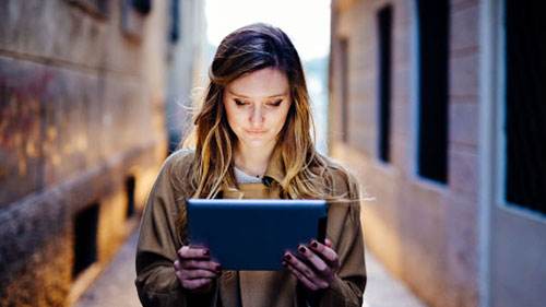 A woman holding a glowing tablet in an alley