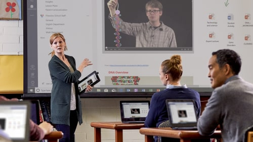 A teacher lectures at the front of a classroom with a tablet