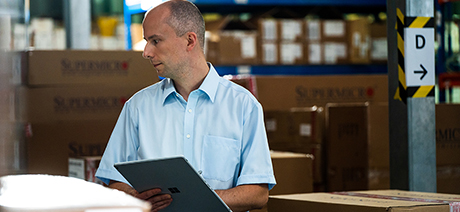 A man with an intense expression takes inventory in a warehouse with the aid of a digital tablet. He wears a short-sleeved shirt and takes his work seriously.