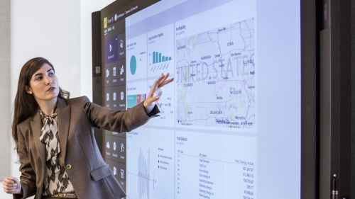 Woman giving presentation pointing at a large screen
