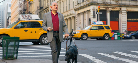 A guide dog leads a well-dressed blind man across a busy city street. The dog appears to be a Labrador.