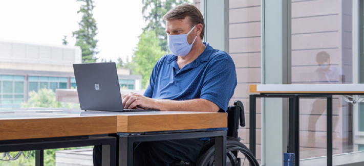 A man in a wheelchair sits on the back porch of his home office. He is working on a laptop and wearing a surgical mask.