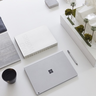 Microsoft Surface laptop on a table next to a cup of coffee