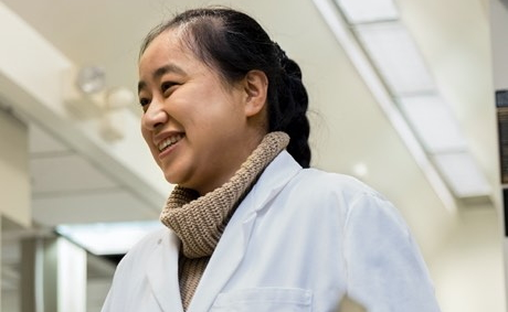 Technician wearing a lab coat and smiling