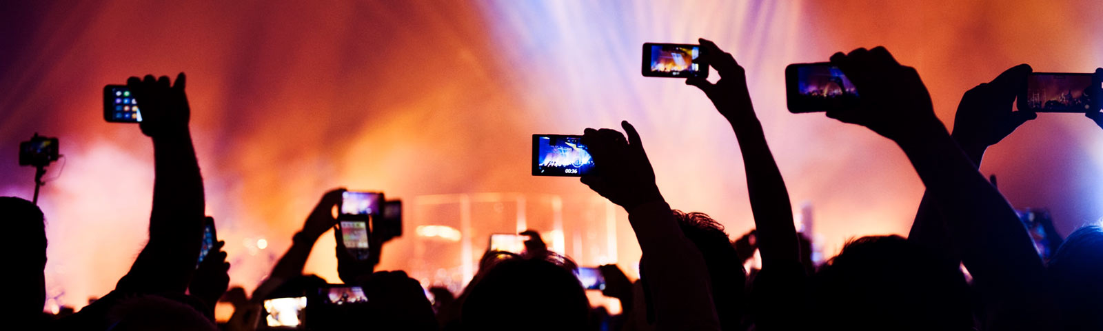 People at a concert raising their phones to record