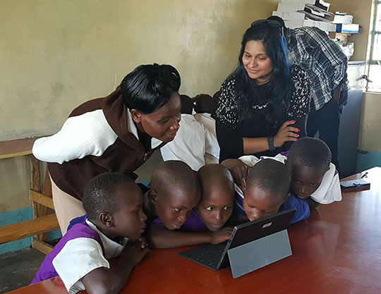 Young school children crowded around a tablet