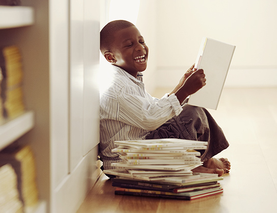 Young boy sitting with books and laughing