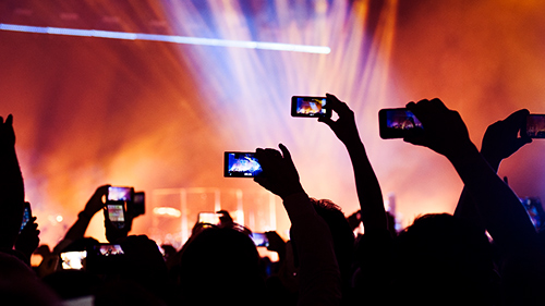 People at a concert raising cell phones