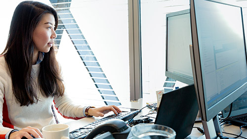Woman working at desk next to window
