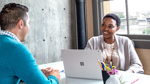 Woman with Surface Book speaking to coworker