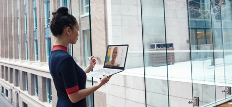 Woman holding a laptop talking on a video call