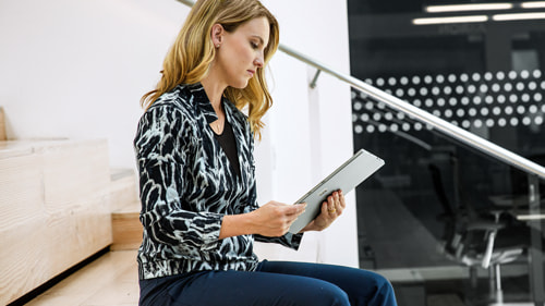 Woman sitting on stairs with Surface tablet