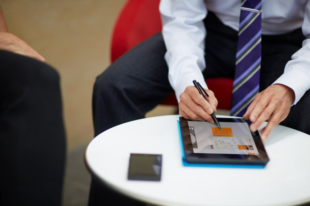 A man wearing a tie working using a computer tablet
