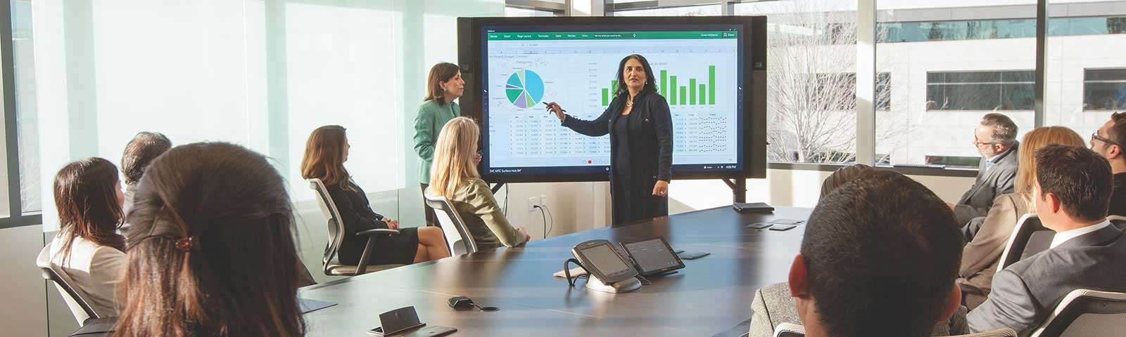 Woman presenting on smartboard in front of coworkers