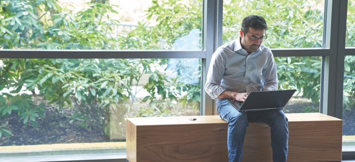 Person sitting on bench using laptop