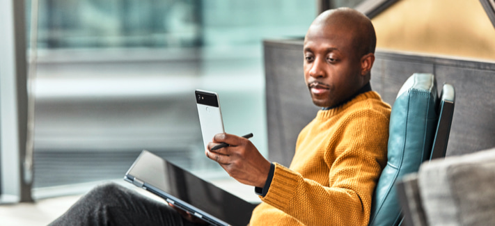 Person sitting in chair looking at mobile phone