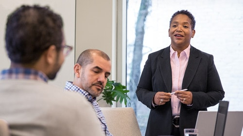 Woman speaking to coworkers in meeting room.