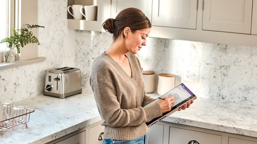 Person standing in a kitchen using a tablet