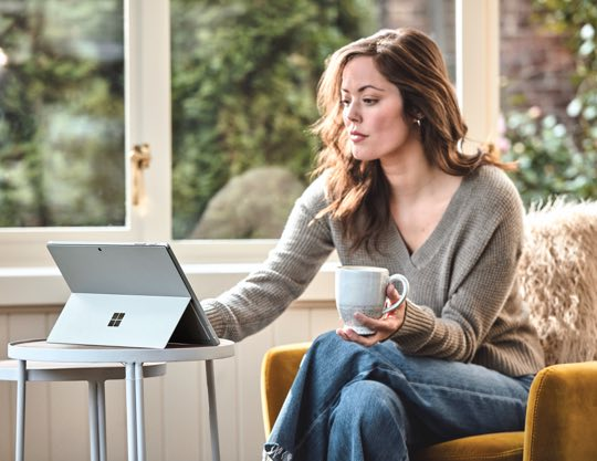 Person holding a mug in one hand and typing on a laptop