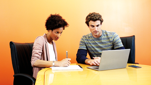 Two people collaborating at desk in front of a laptop