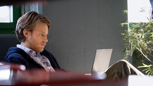 A man sitting in a lounge chair looking at a laptop
