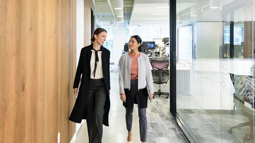 Two women walking in an office
