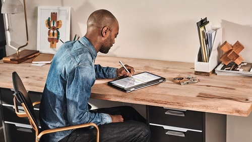A man working on a tablet in his home office