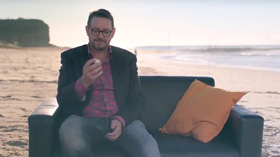 Man talking to camera while sitting on a couch on the beach