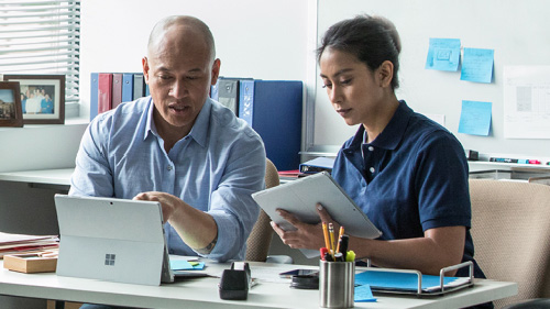 Man and woman collaborating while working inside office