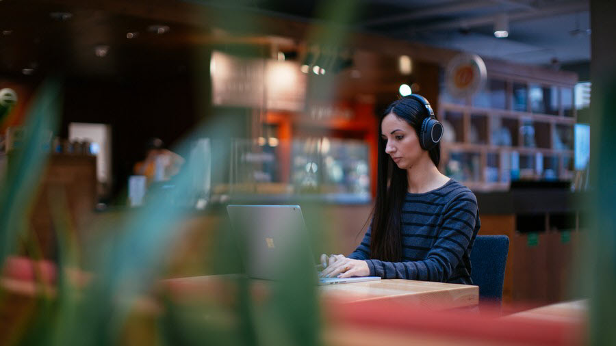 Woman with headphones working in coffee shop