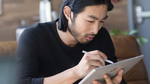 A man works on a design document on his tablet
