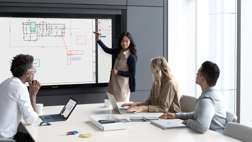 Four people watching a presentation on a whiteboard