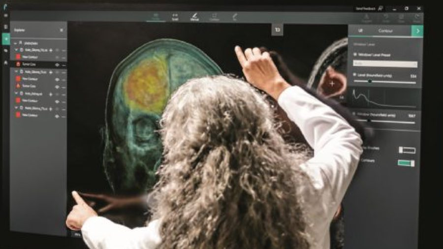 Person using a large touch screen display showing images of an MRI brain scan
