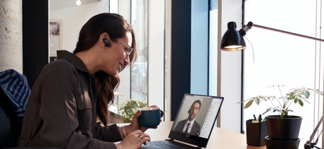 Woman drinking a cup of coffee on a video conference call